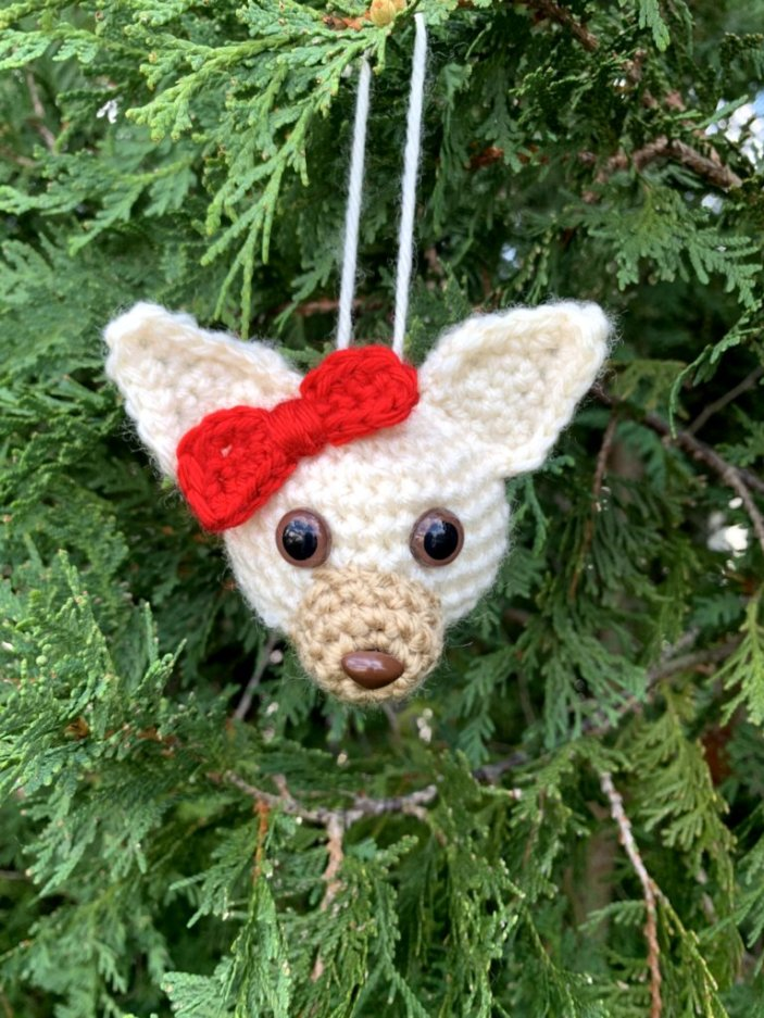 Hanging Puppy Dog ornament in a cream color with pointed ears and red bow on its head, hanging from a pine tree.