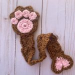 A brown paw print flat crocheted bookmark.