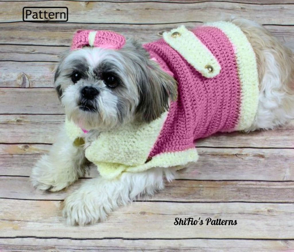 A Shih Tzu laying on a wooden floor wearing a pink crocheted jacket and wearing a bow.