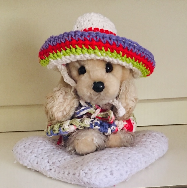 A stuffed dog modeling a crocheted poncho and sombrero.