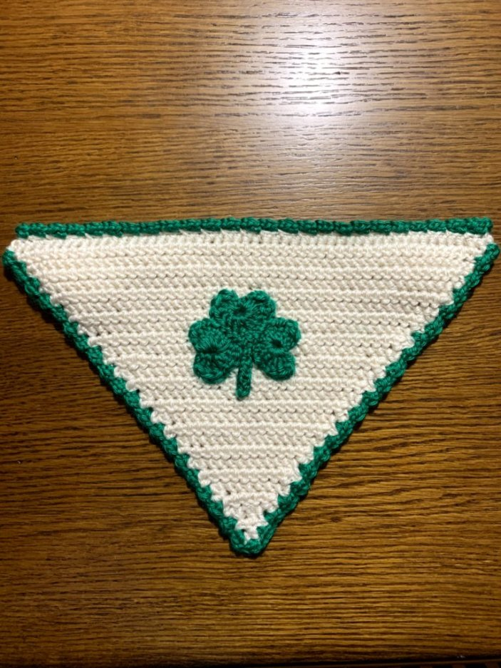 Crochet Shamrock Dog Bandana laying flat on a wooden table