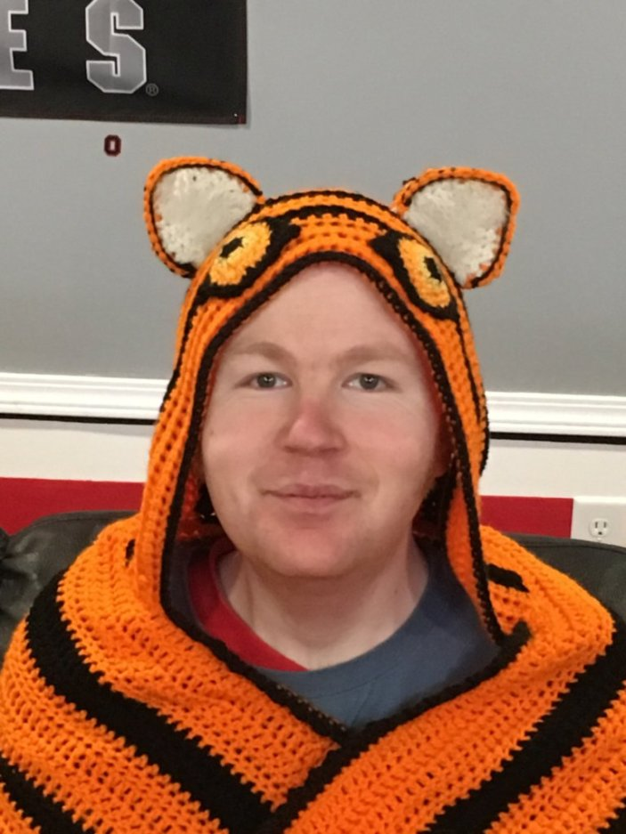 Close up picture of young man in wearing the hood of a Hooded Tiger Blanket.