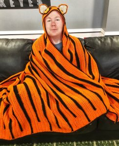 A young man sitting on a black leather couch wearing a crochet Hooded Tiger Blanket.
